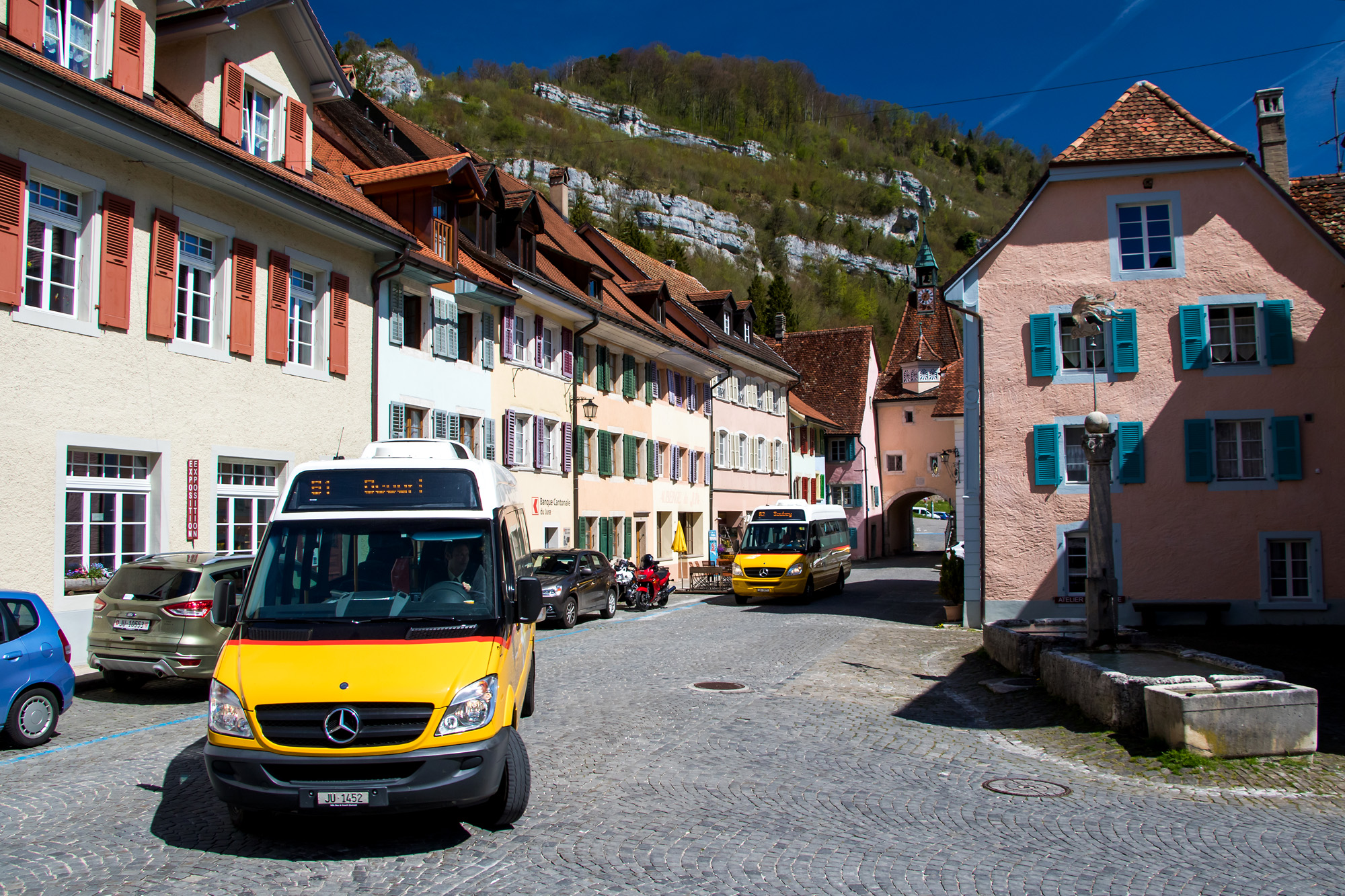 Postauto-Umzug der zwei Mittagskurse durch die Altstadt von St. Ursanne (JU)