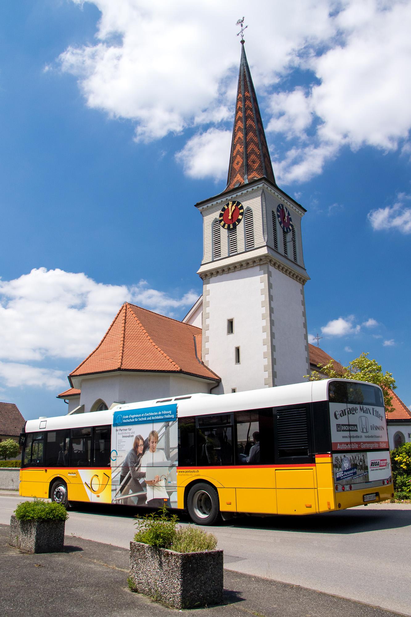 Das Postauto nach Düdingen passiert die Kirche von Gurmels, die in Teilen von 1605 stammt