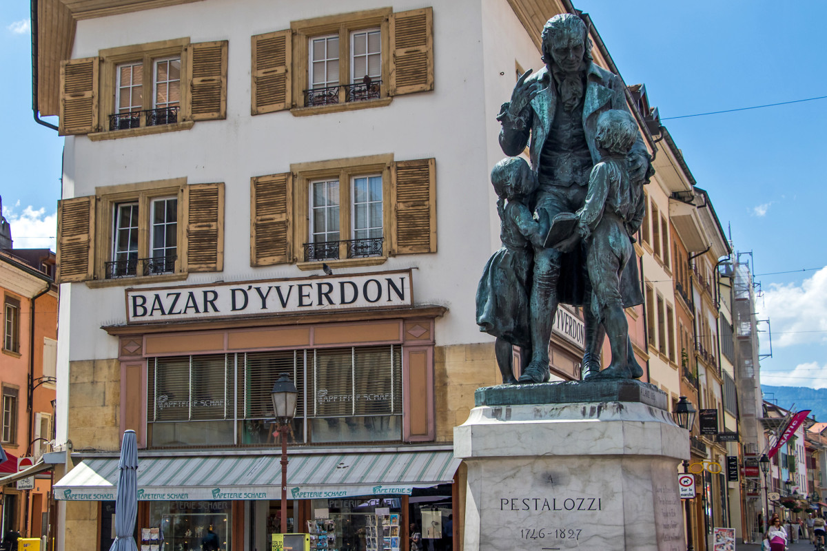 Pestalozzi-Denkmal auf dem gleichnamigen Platz. Die Stadt Yverdon kaufte seinerzeit die Burg, um dem renommierten Pädagogen dort eine Schule einzurichten. Von dort aus verbreitete sich sein Einfluss bis weit in die Nachbarländer