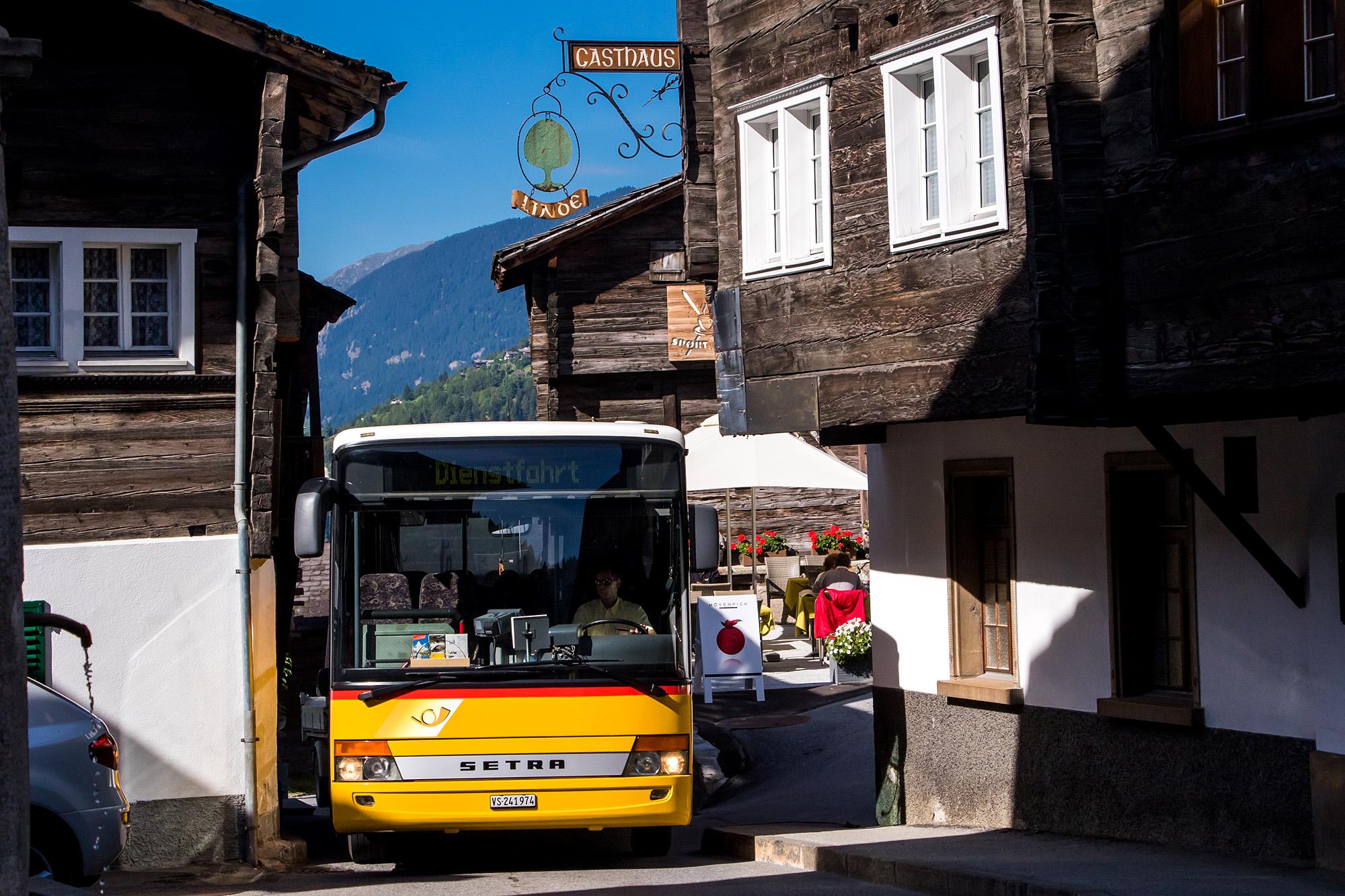 Passgenau zirkelt das Postauto durch den Dorfkern von Ernen, VS
