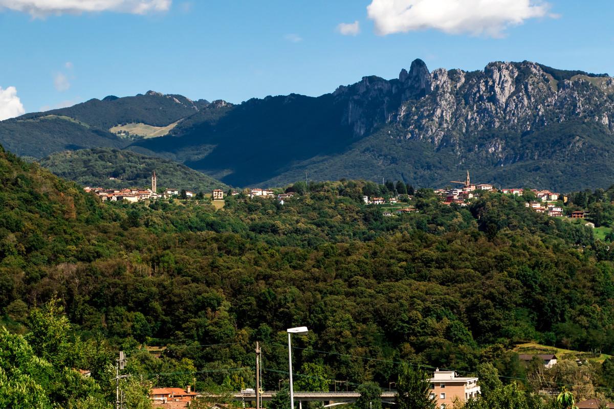 """Blick auf die andere Talseite: Hier posieren die Dörfer der Gemeinde Capriasca vor der Felsformation """"Denti della Vecchia"""""""